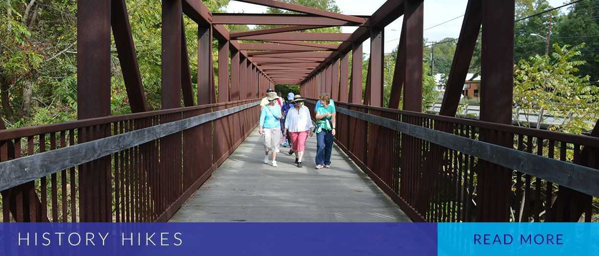 Hikers walking across bridge at West Point on the Eno Park