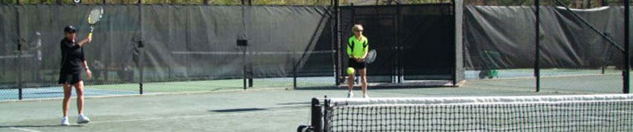 Two adults playing in a tennis match