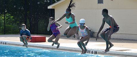 Group of Children Jumping into a Pool Together